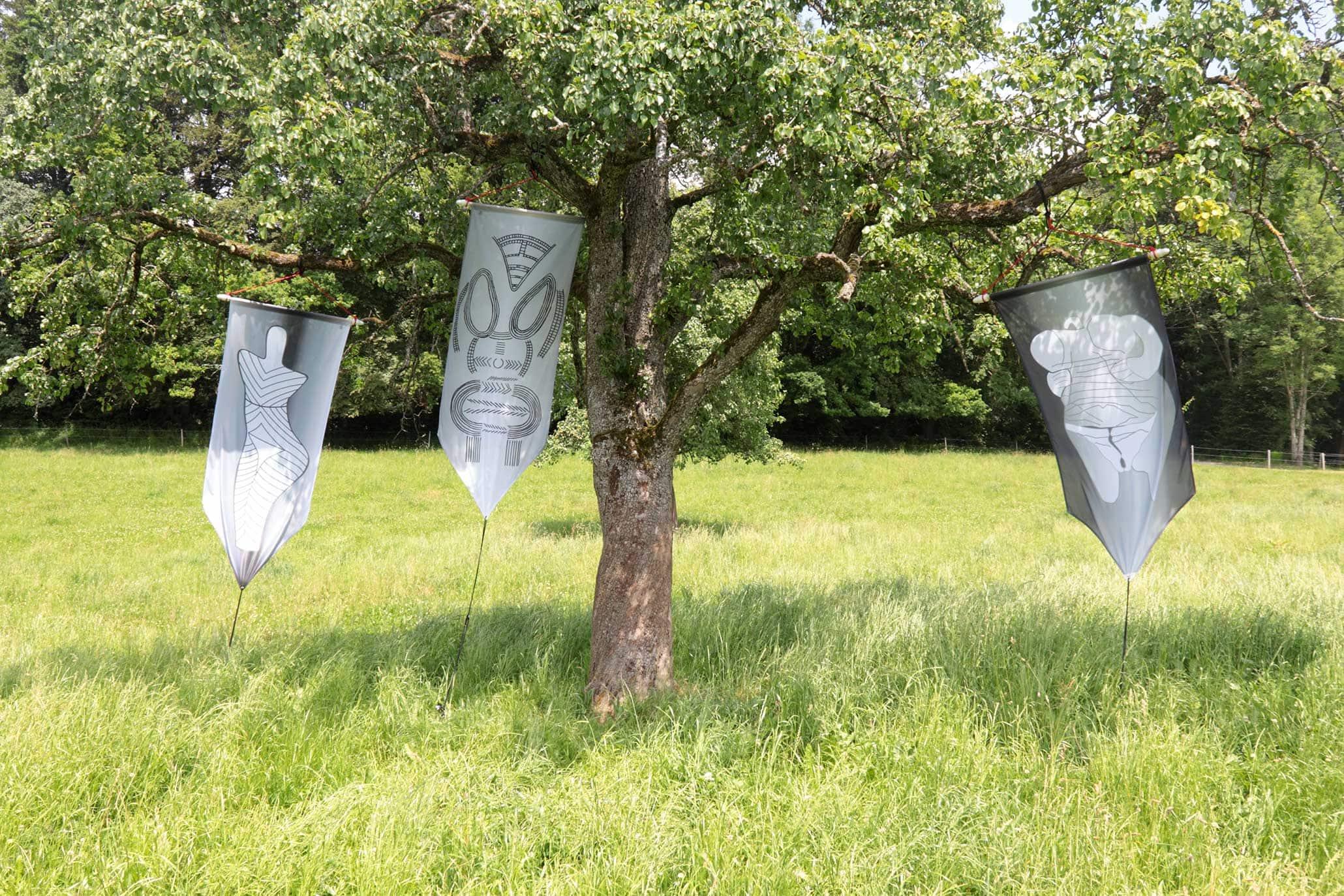 Ausstellung im Freien, auf dem Panoramaweg in Toggwil, Meilen (Zürich), Schweiz, 2014. Drei GLOBAL-VULVA-Flaggen an einem Baum.